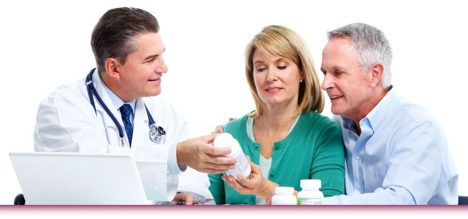 pharmacist going over medications to older couple